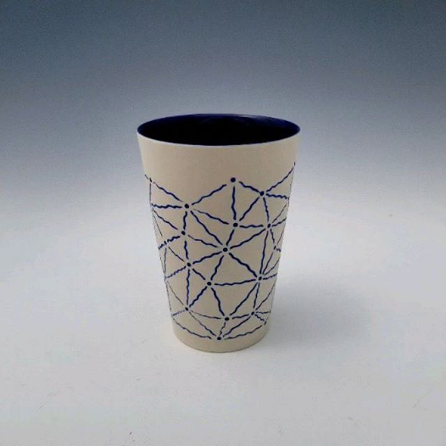 Available. Link in bio. Swipe to see a few process shots. The first is before I inlaid blue underglaze into the carving and the second is after.  This cup is one of my newer slipcast forms. It's a pretty simple shape, but it provides a nice blank canvas on which to carve designs. I've found I'm much more willing to try different design approaches when working with slipcast forms over ones I've thrown on the wheel. The time investment in just getting a cup to carve is less, so I can focus more on the surface design. What do you think? Do you have a preference for one method of making over the other?  Check out my other account @the_line_rider