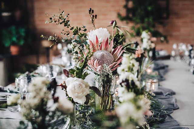 Details from one of our favourite wedding table settings to date.  Glittering glass globes carrying candles and moss floated off a suspended olive branch centre piece. Flower posies with peonies berries and proteas filled the space and a gorgeous lavender runner swirled around the hessian wrapped candle jars.