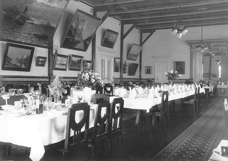 The classy dining room at Kviknes Hotel. Hotel guests could watch stunning paintings while enjoying their dinner. The art is still at Kviknes Hotel today.
