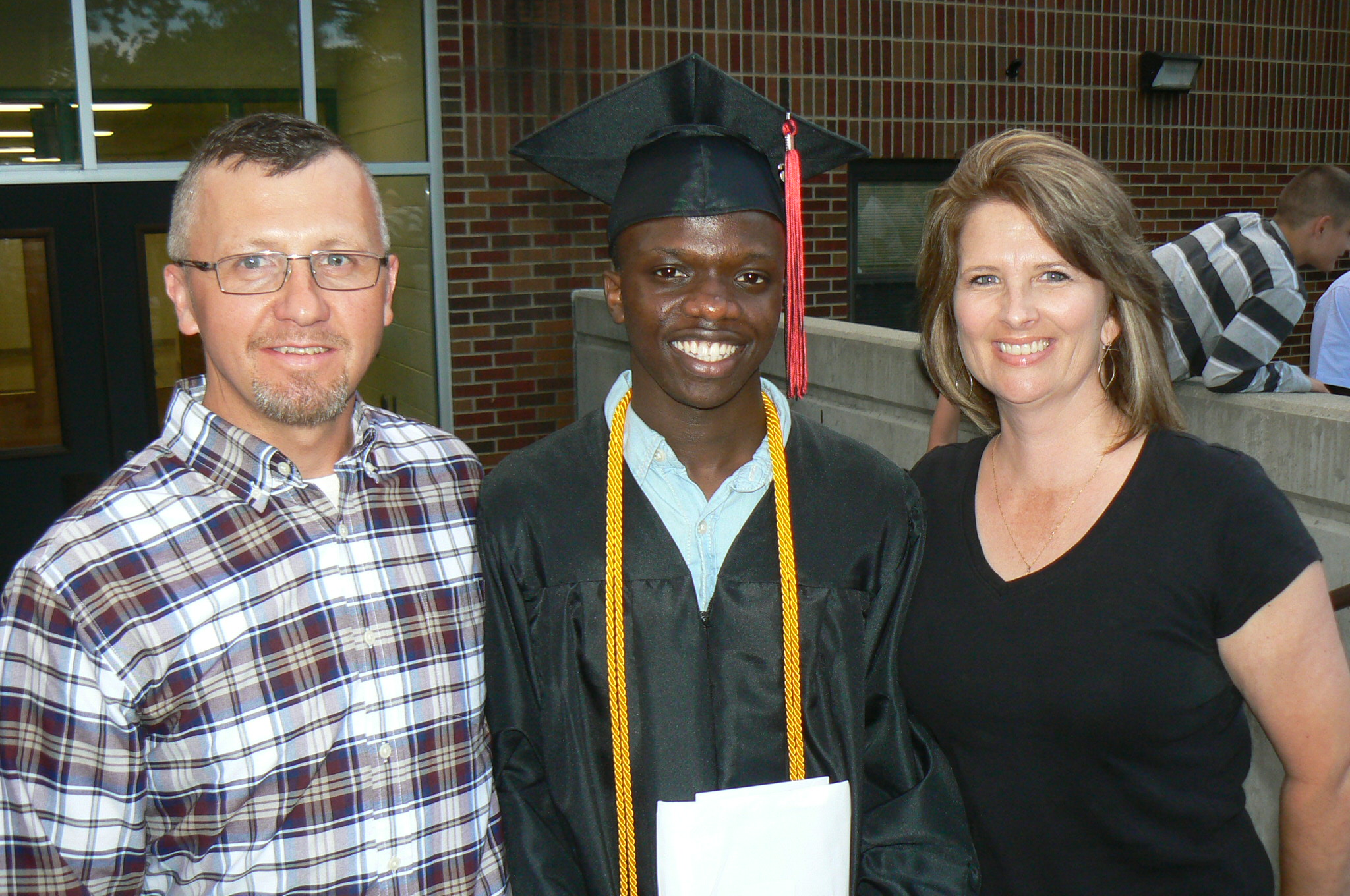 Jerry at his high school graduation with his former houseparents Jake & Tracy