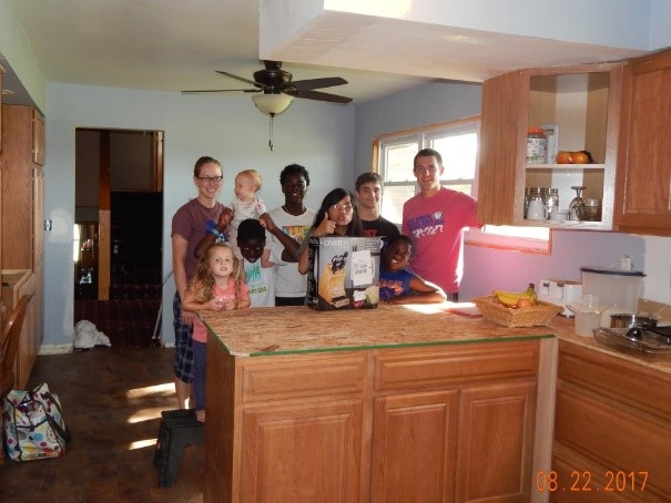 Some of us pose for a picture with a generously donated knife set in our partially completed kitchen.jpg