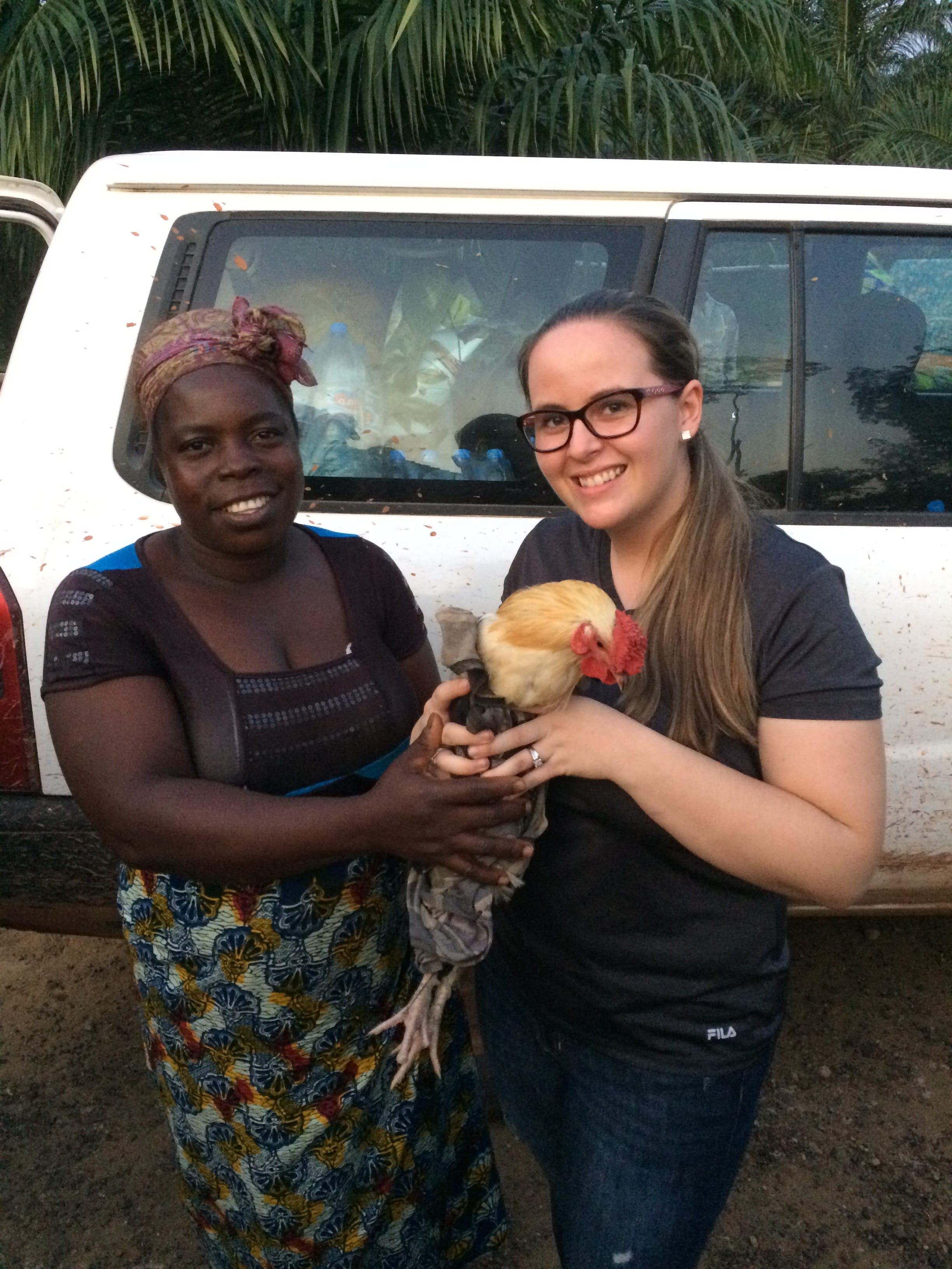 Hillary holds the chicken presented to us by the village of Mehla