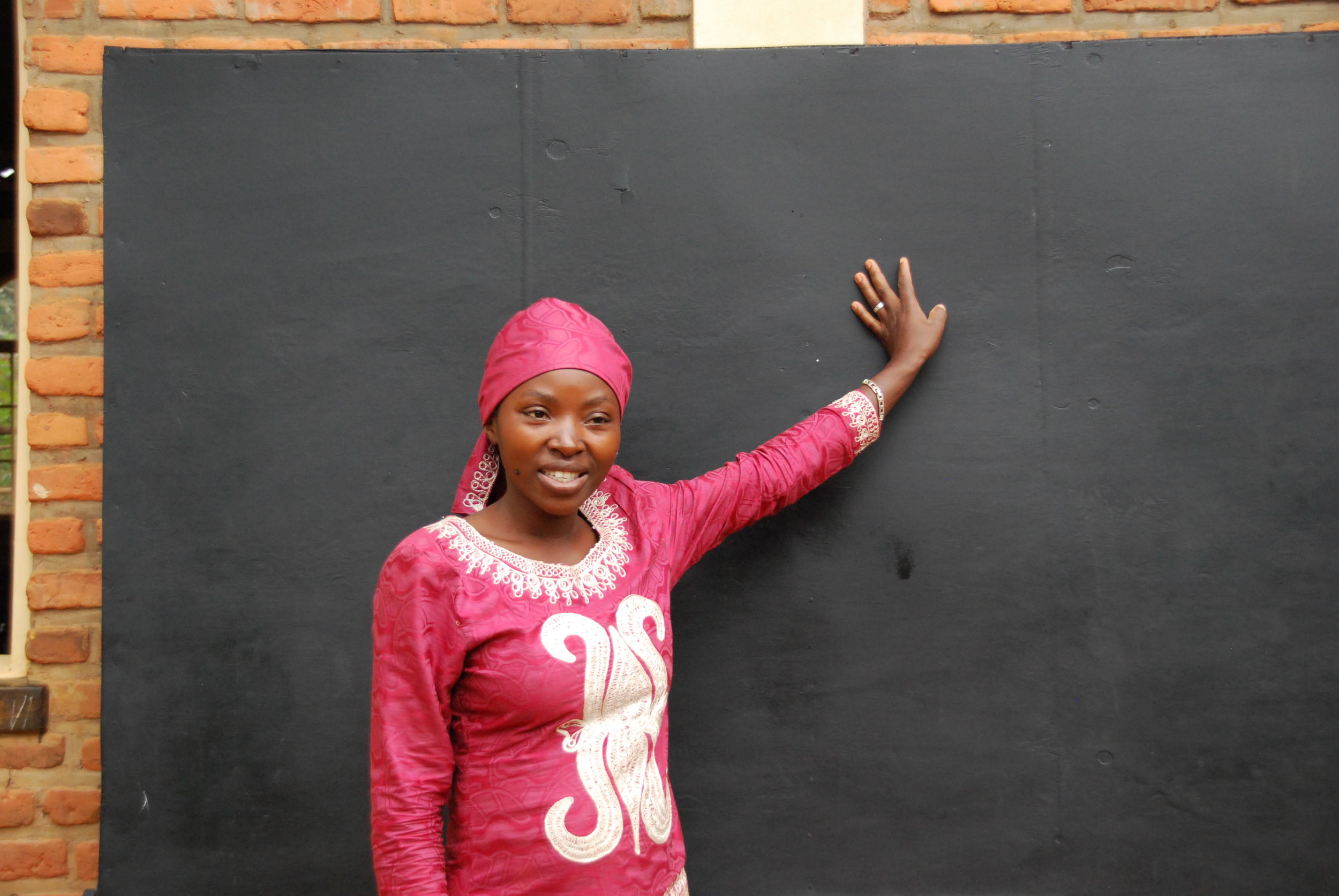 Jane, the Nkombo island teacher, standing with her new chalkboard for their class!