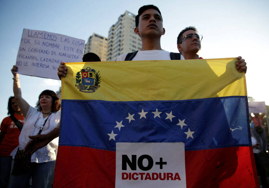 an-opposition-supporter-holds-a-venezuelan-flag-with-a-sign-that-reads-no-more-dictatorship-during-a-protest-against-venezuelan-president-nicolas-maduro-s-government-in-caracas-venezuela-march-30-2017-reuters-marco-bello.jpg
