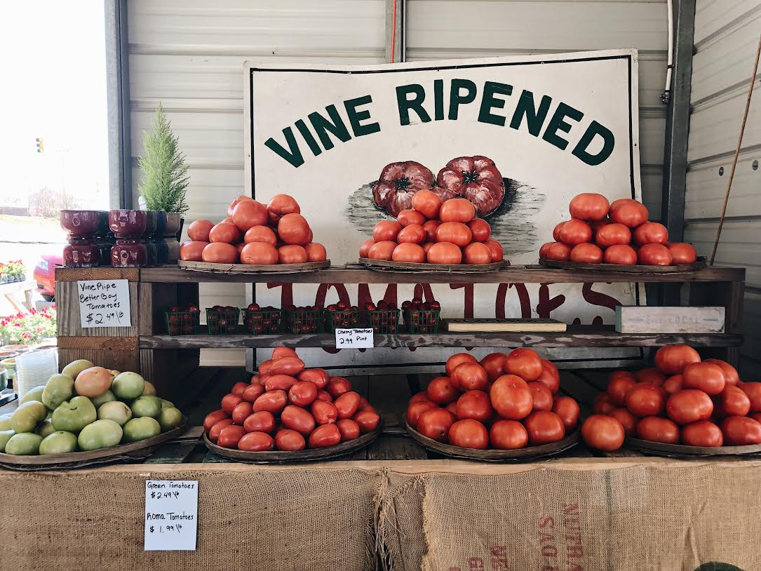vine ripened tomatoes sign with tomatoes display underneath
