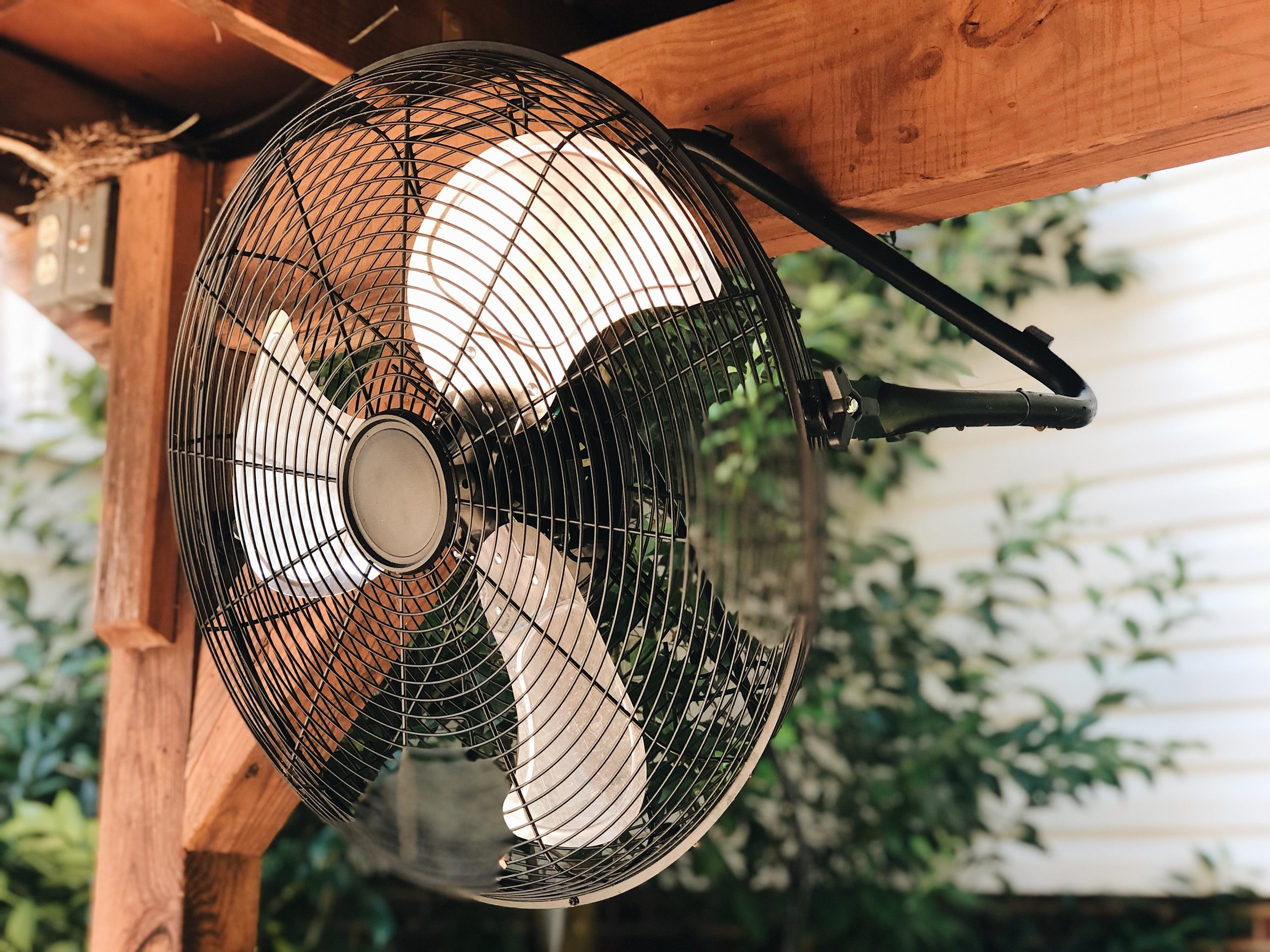 fan hanging from brown wood