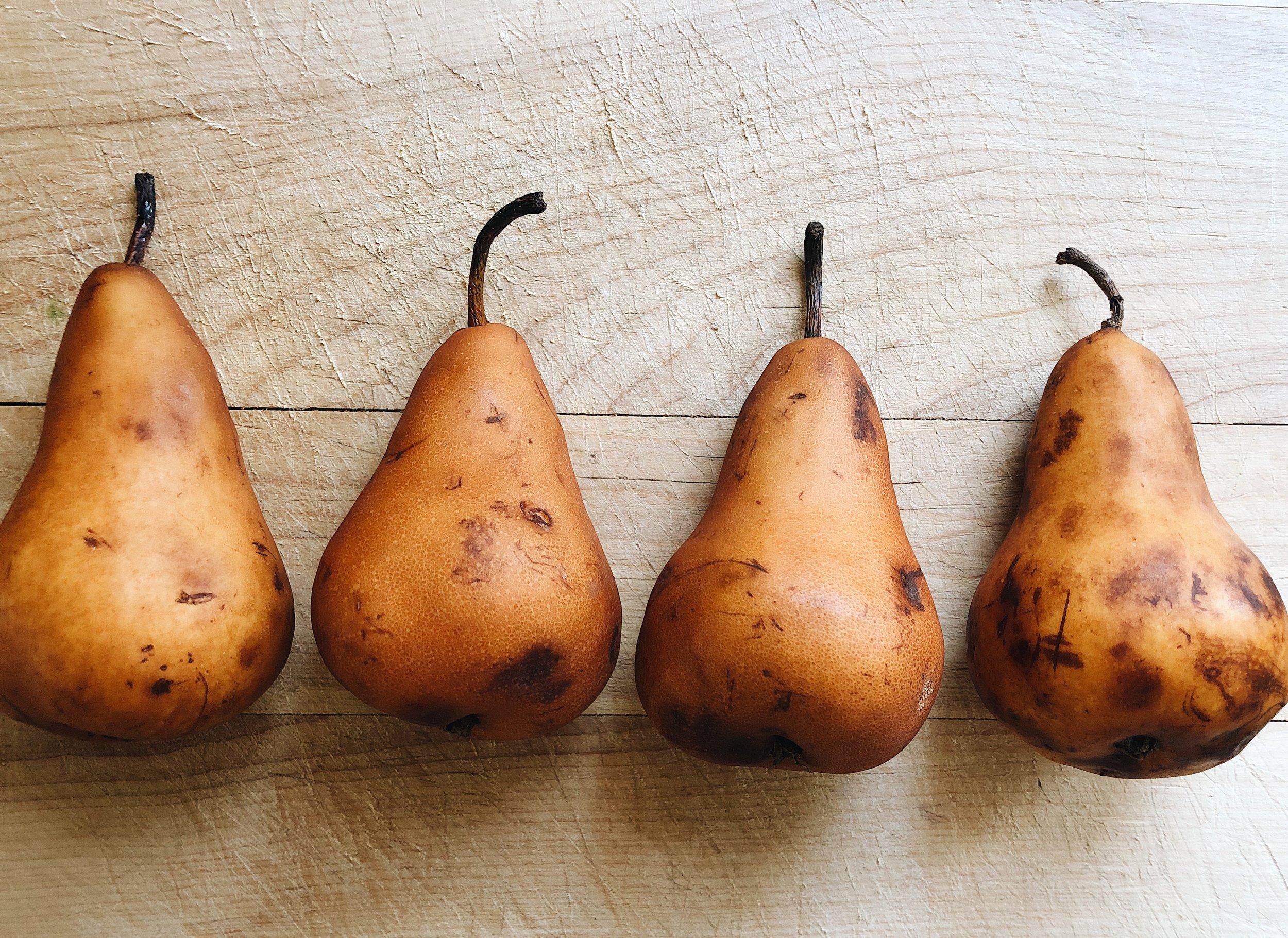 brown pears laying on wood cutting board
