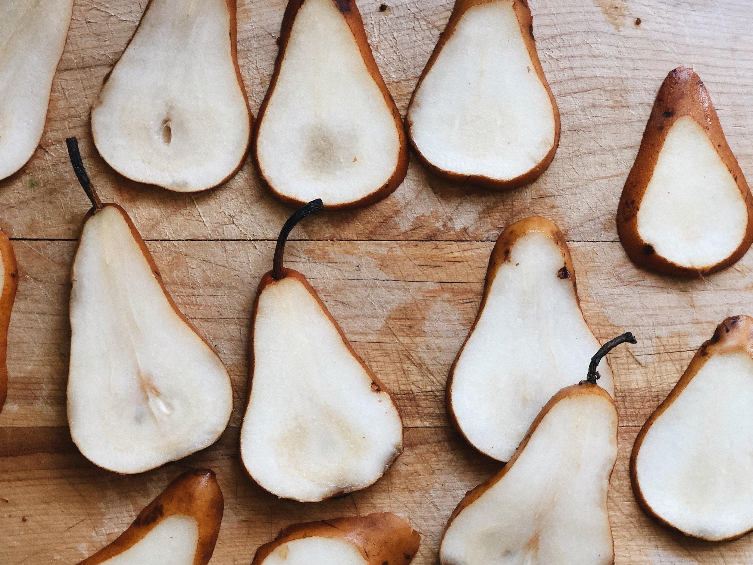 cut pears laying on wood board