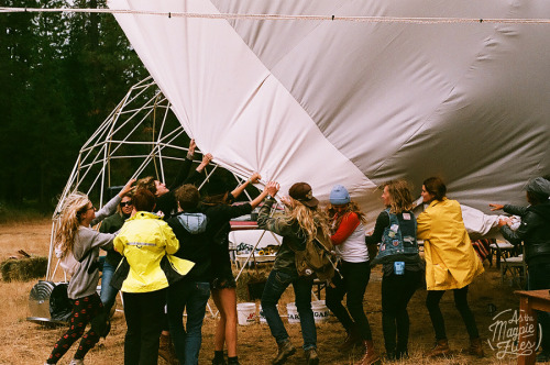 Women working together to save the tarp off of the Escape Collective Dome Saturday Morning.