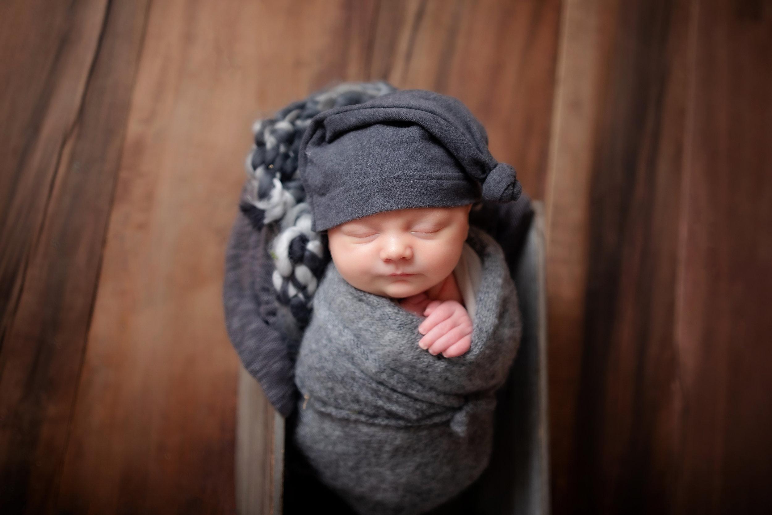 Newborn in gray wrap
