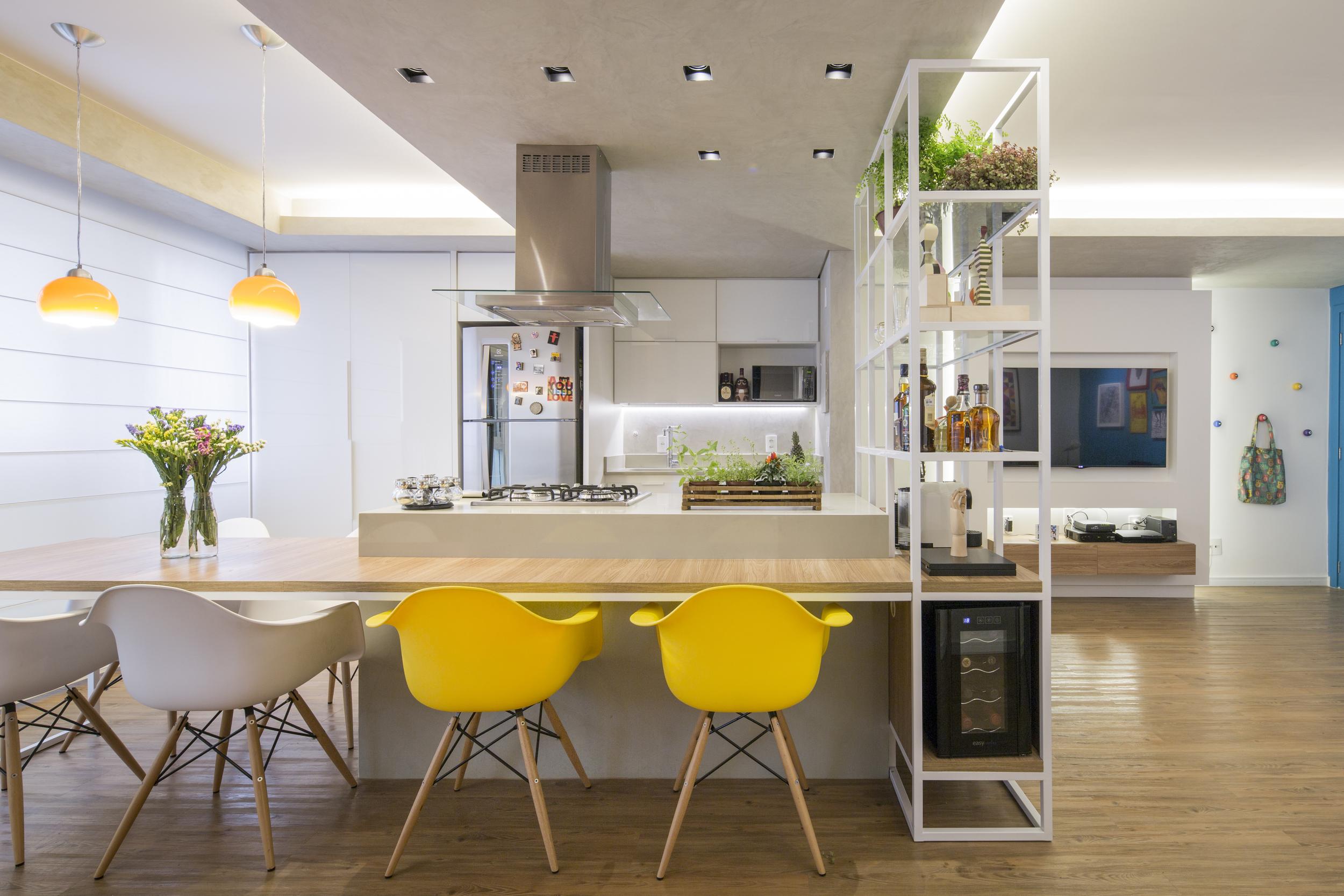 Um só elemento multifuncional, abraça a ilha da cozinha e se torna o coração do projeto.