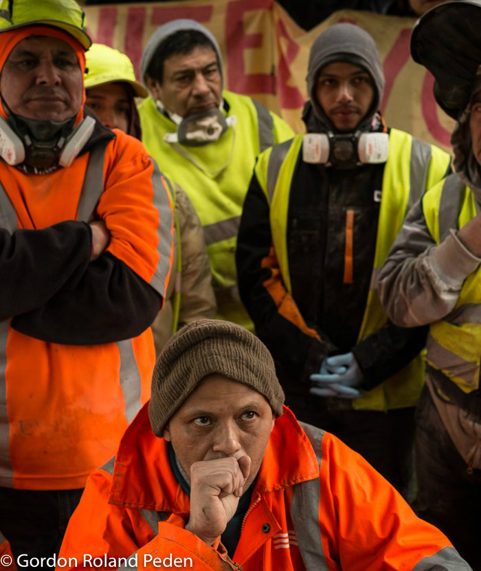 - Peruvian workers at the Orion waste disposal and recycling facility in east London were being ruthlessly exploited. Paid the minimum wage for their labour in dangerously dusty enclosed spaces with insufficient respiratory protection, they were united in their readiness to walk off the job — within 24 hours of their first meeting with a UVW caseworker.On that chilly morning, the company owner was confronted by a workforce unwilling to lift a finger until basic demands were met. A group of UVW staff and supporters joined them in asking the questions for which there was no rational response except to pledge to provide, the very next day: proper face masks, air filters, gloves, four pairs of protective overalls each, soap and toilet paper — and to install on-site showers within a month. This was all readily agreed to by a flustered and unprepared owner.They also won a pledge to discuss a significant pay raise to the London Living Wage, plus occupational sick pay — meaning that they would get appropriately paid for their first 3 days of injury or illness, instead of nothing at all!On top of that: a personal apology from the site manager, and a promise that for the day of this wildcat strike they would still be paid and not victimised! A momentous result for workers who had never before been members of a trade union…