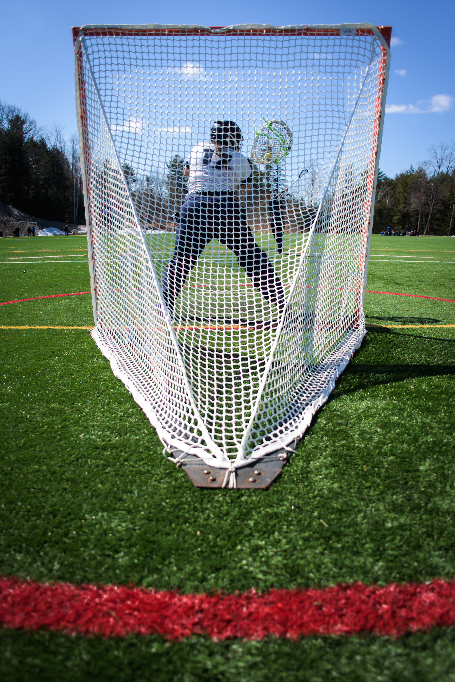 Huskies goalkeeper Caley Presby fields practice shots at the USM lacrosse field in Gorham, Saturday, March 26, 2016.