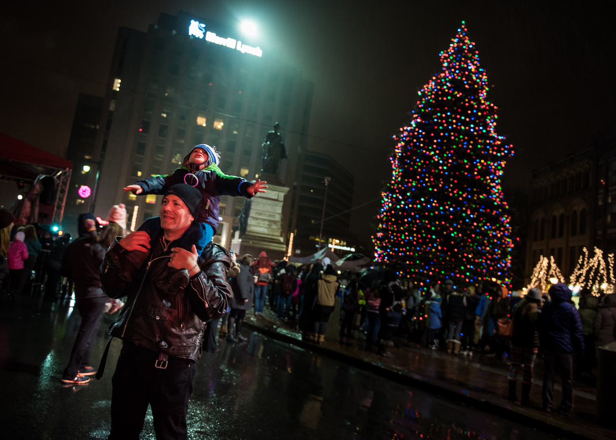Jeffrey Blood and his son Miles, 3, of Westfield, Mass.stand in front of the Portland Christmas tree moments after it was lit Friday, November 25, 2016 in Monument Square.
