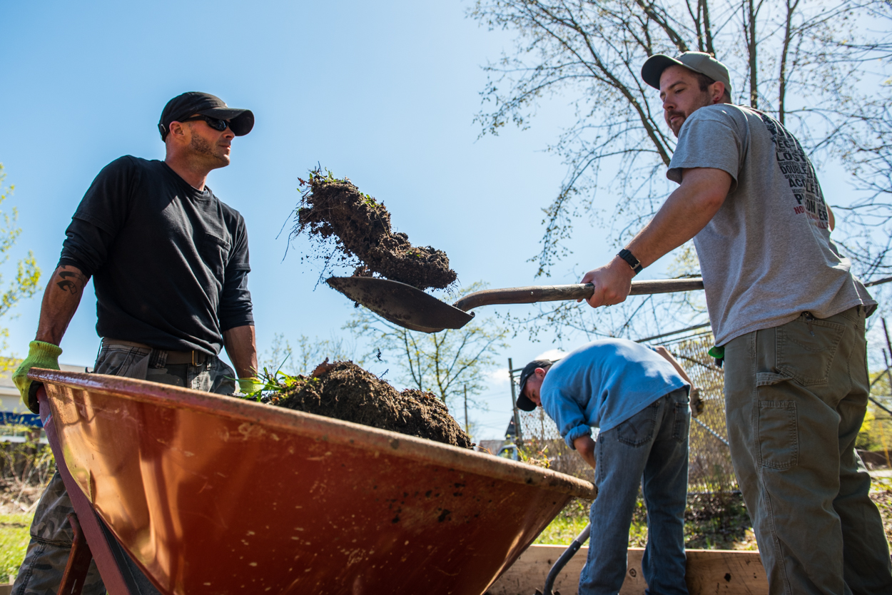 Sean Jenkins, standing at left behind wheelbarrow, Cecil Solaguren, tossing dirt, and Brian Hall, shoveling at rear dig out a planter box at a new community garden in the North Deering neighborhood of Portland Sunday, May 7, 2017. The garden aims to bring together individuals in recovery from alcoholism and drug addiction.