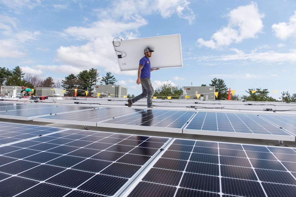 Jack Doherty of ReVision Energy carries a solar panel across the roof of Maine Historical Society's offsite collections management facility in Portland Wednesday, April 18, 2017.