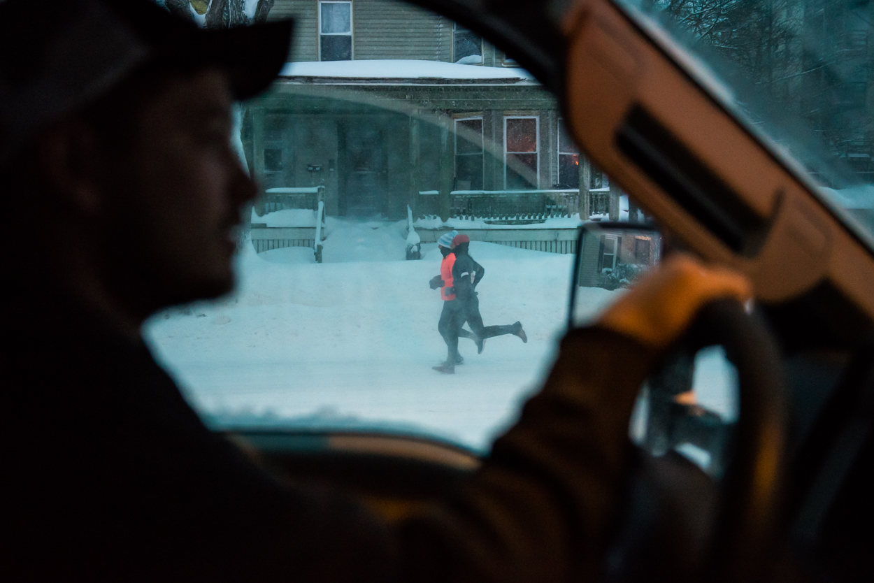 A pair of joggers get their morning exercise on Park Avenue in Portland as Dave Blackwell of the city's Parks and Recreation department clears parking lots Monday, February 13, 2017.