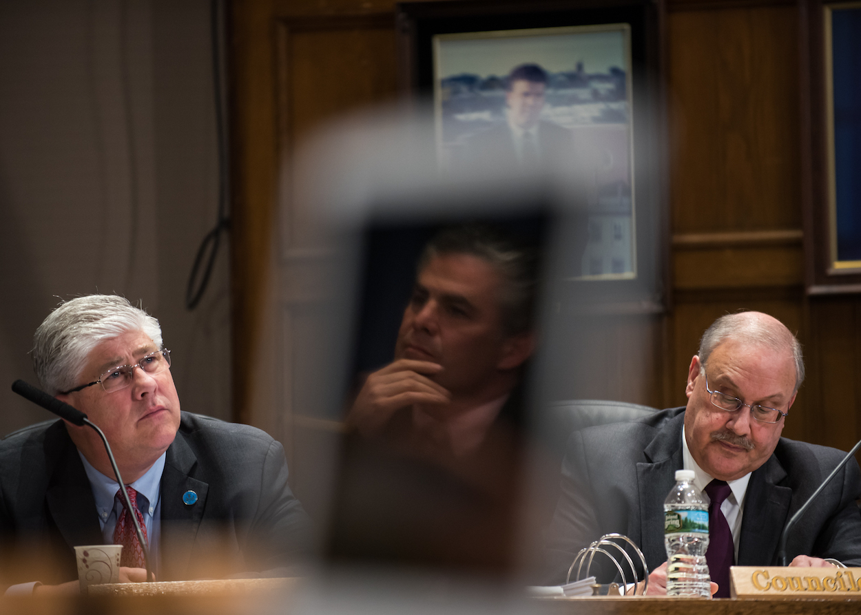Portland city councilors Nicholas Mavodones, left, David Brenerman, and mayor Ethan Strimling, reflected in the laptop screen of councilor Brian Batson, listen to addresses from residents at a City Council meeting at Portland City Hall Monday, March 27, 2017.