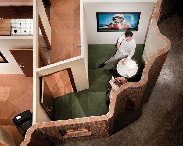 Casa en forma de España destechada y detalle de habitación