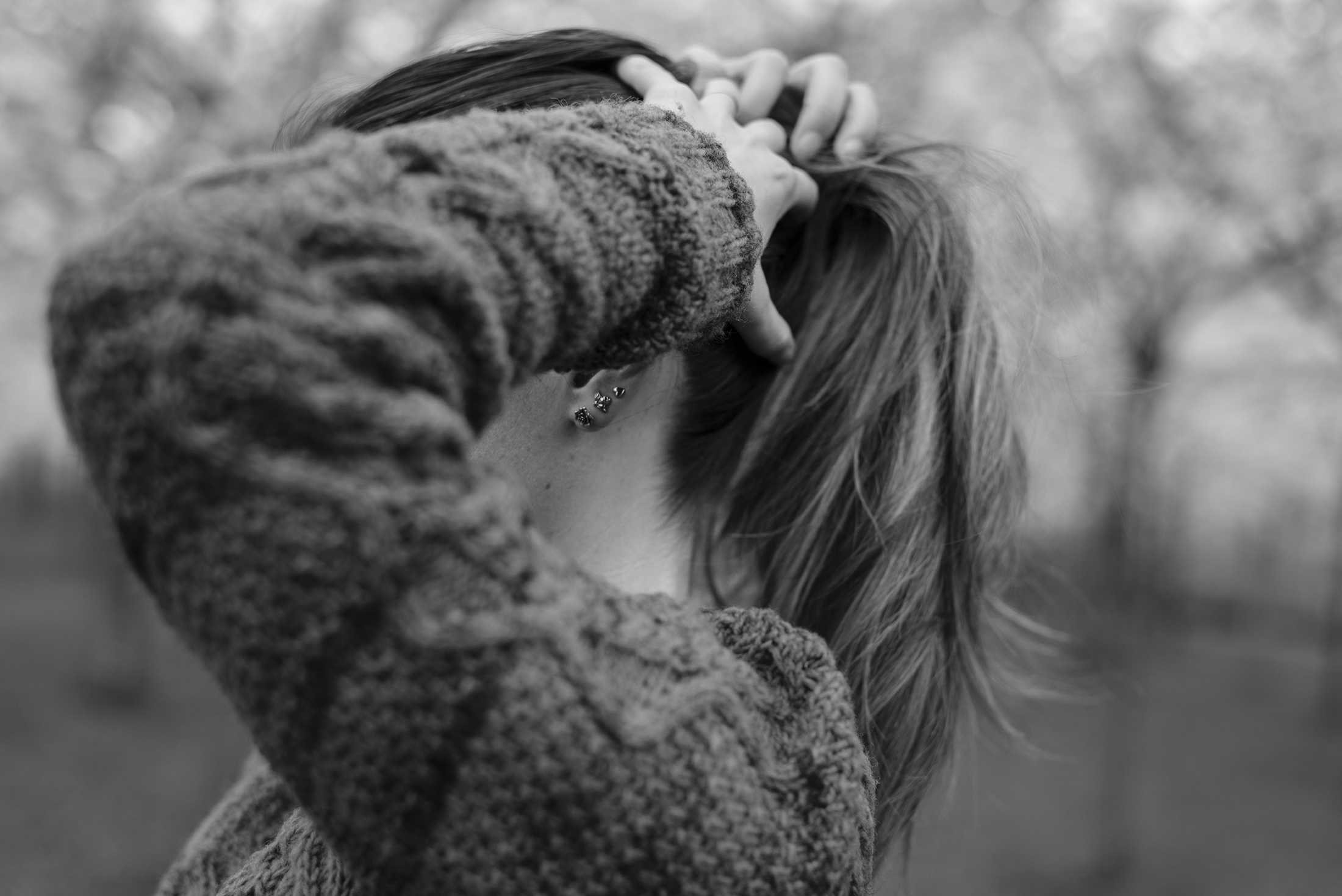 holding hair close up black and white photography