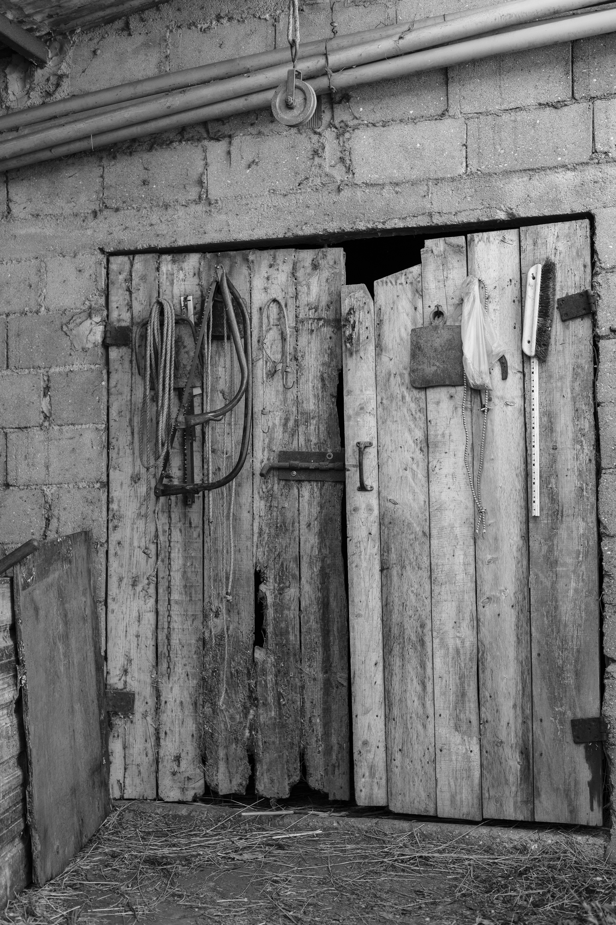 old barn gate with tools black and white still photograph