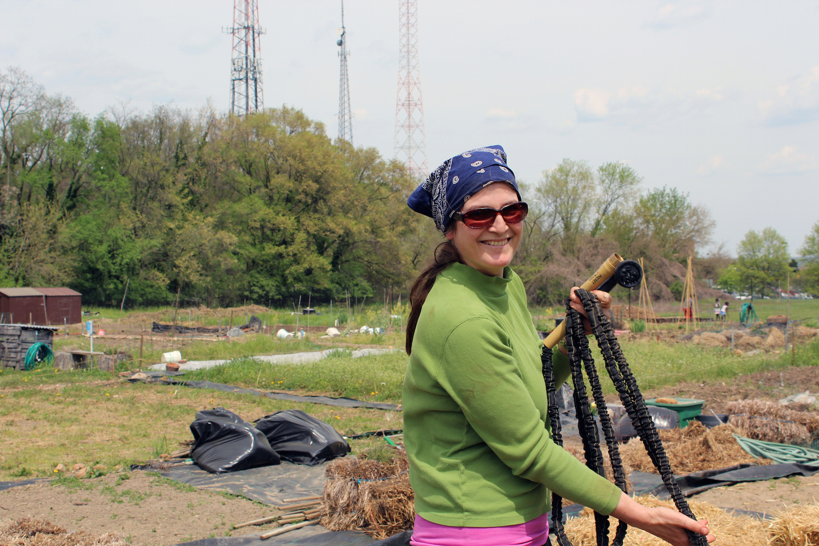 Ingrid Wood, a community garden plot owner at Fort Totten Urban Organic Garden in northeast D.C., waters her 25-by-25 foot garden plot. (Photo by Robin Dienel.)