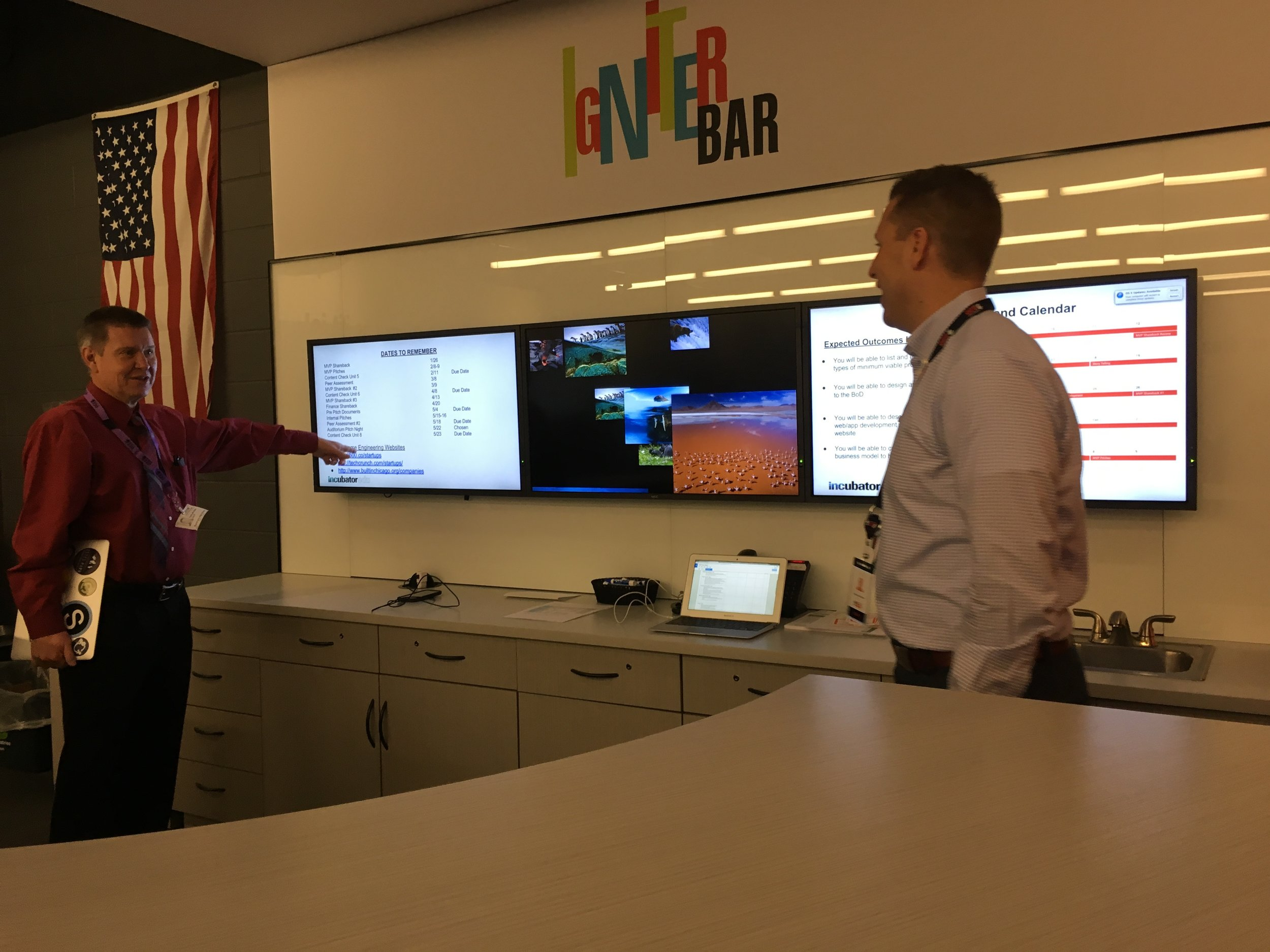 Director of Technology, Kevin Aten, inspects student business plans with a staff member from Barrington Schools.
