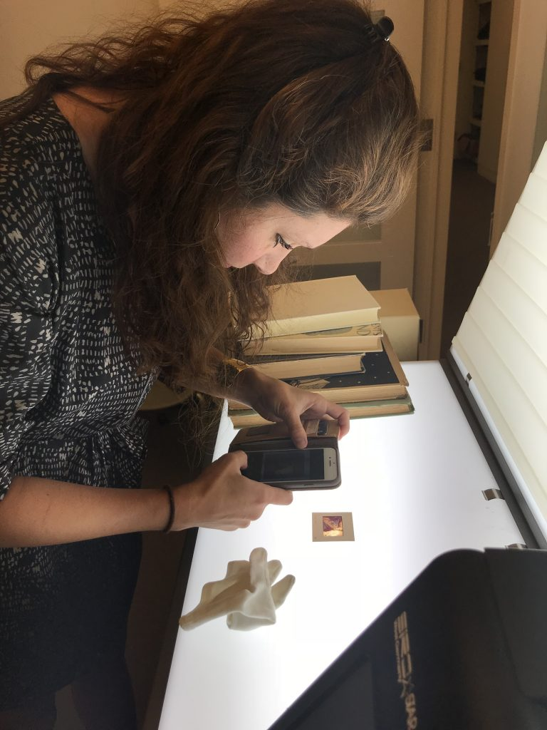Rachel Reese looks over 35mm slides of Suzanne Jackson's work from the 1980s on the light table in the curatorial offices at Telfair Museums. Photo: Dana Melaver