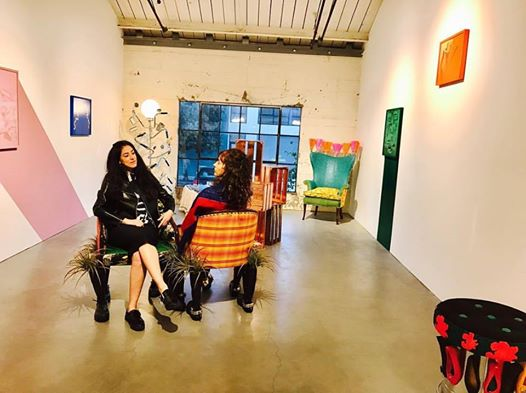 """Carola Zertuche (l) and Lorena Zertuche (r) seated on Lorena's """"Courting Bench"""" on display during her 2016 exhibit at the Minnesota Street Project"""