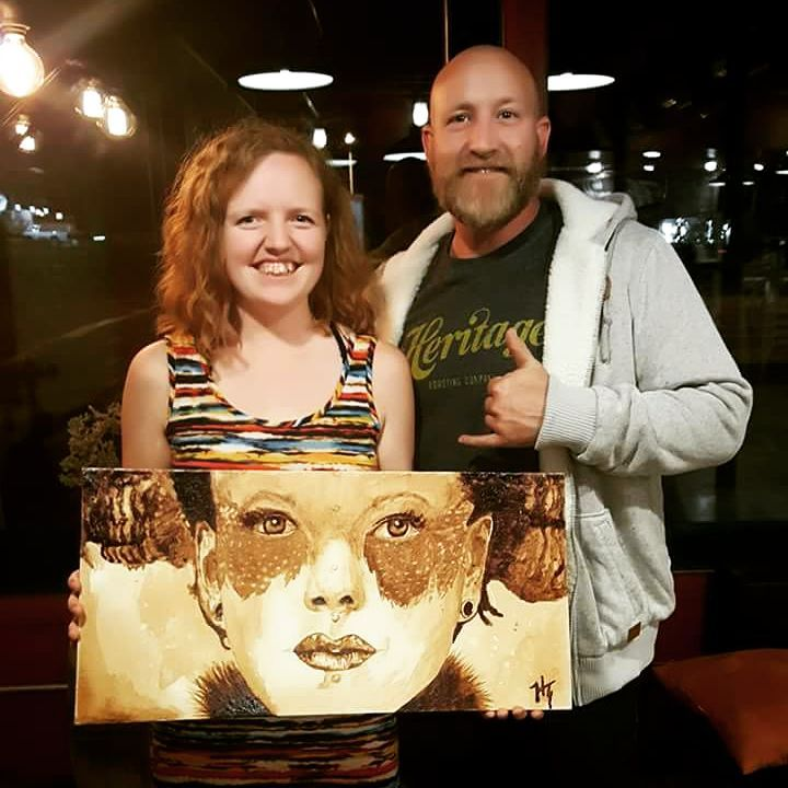 Artist, Hannah Townley, standing with the Tim Lee, the winner of this piece, 'Safe to Shore', painted with coffee. He won it through a Silent Auction held at Heritage Roasting Co.