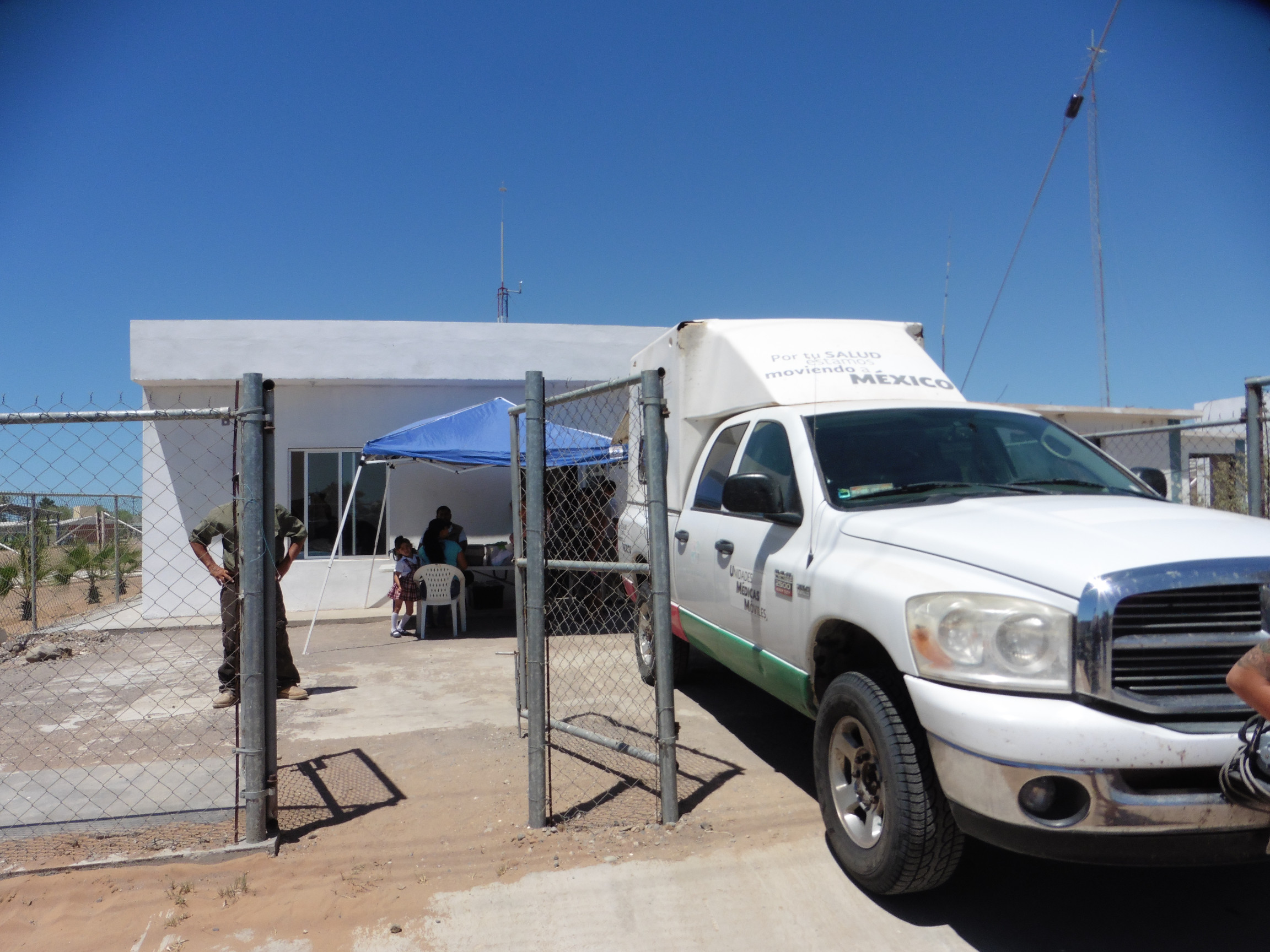 A white Dodge truck with a tailgate cover acts as a traveling office and storage closet for the local doctor on call.