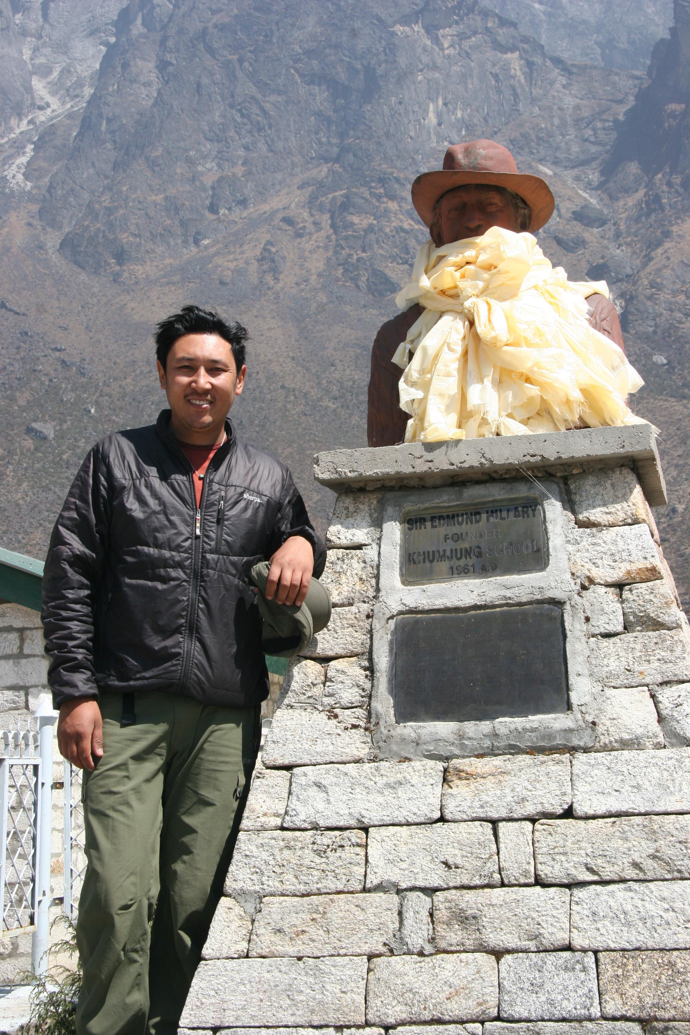 Mingma next to statue of sir edmund hillary