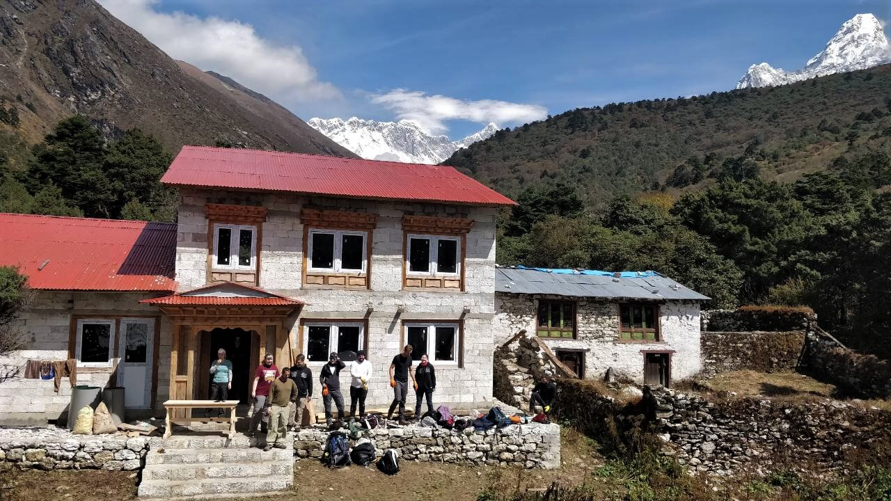 fall 2018 volunteers in front of building with Everest in background and ama dablam to the right.jpeg