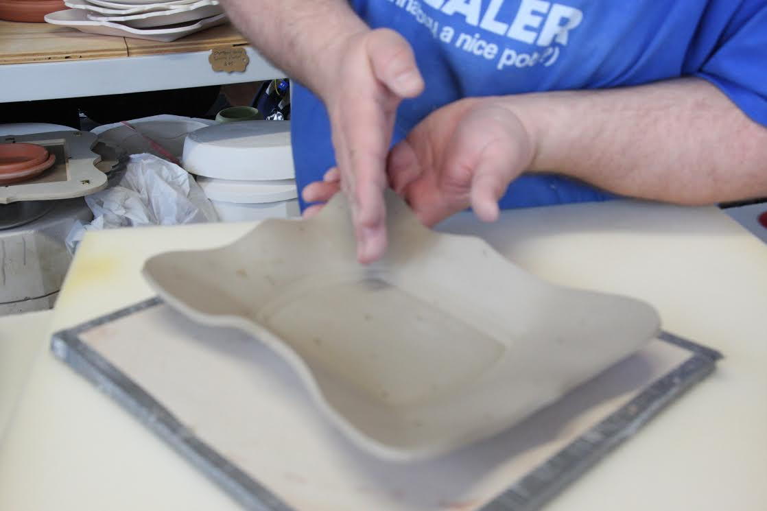 Balancing the pressed piece before covering it with plastic to dry slowly.