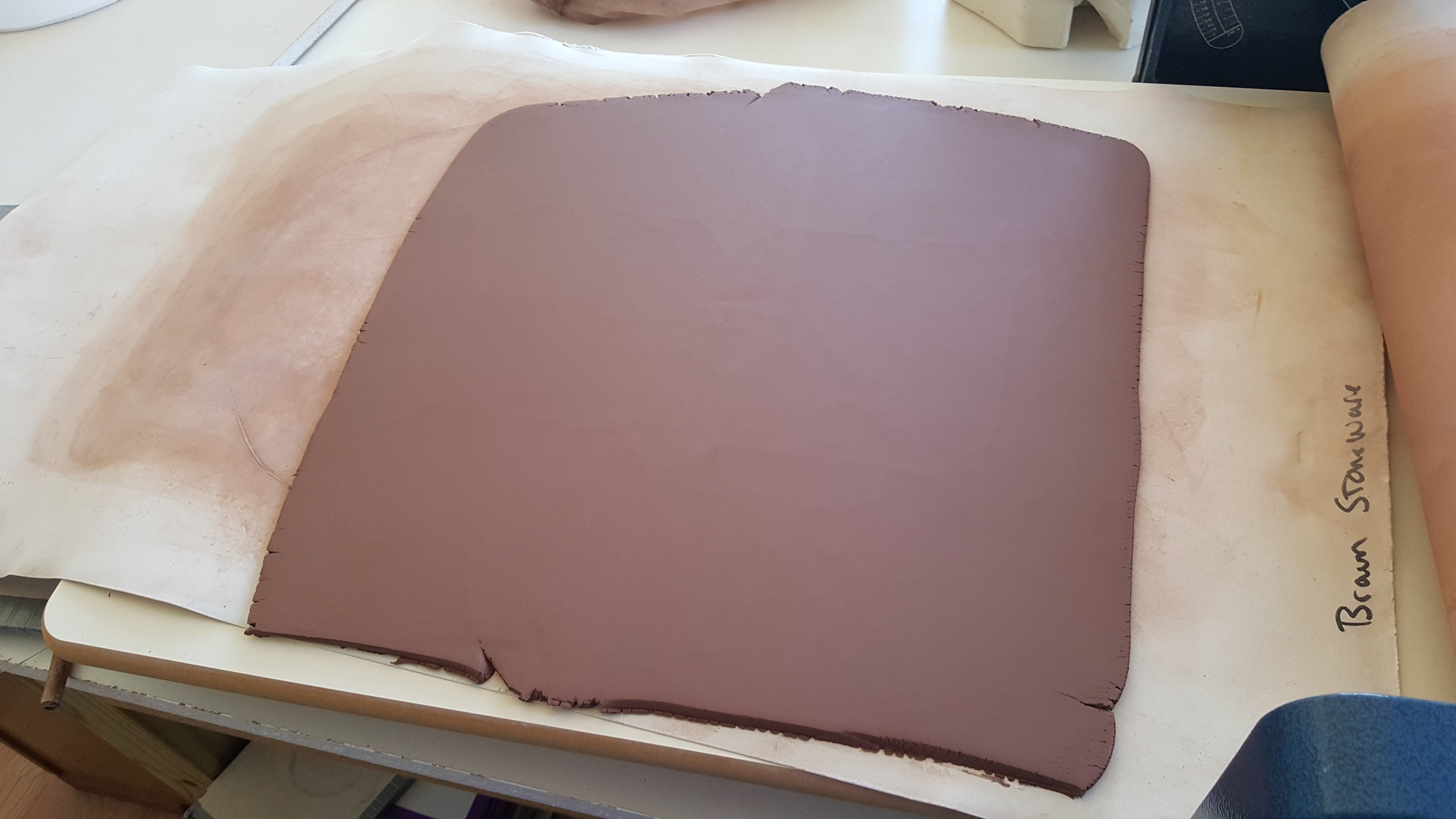 Red clay rolled out and ready to be formed.