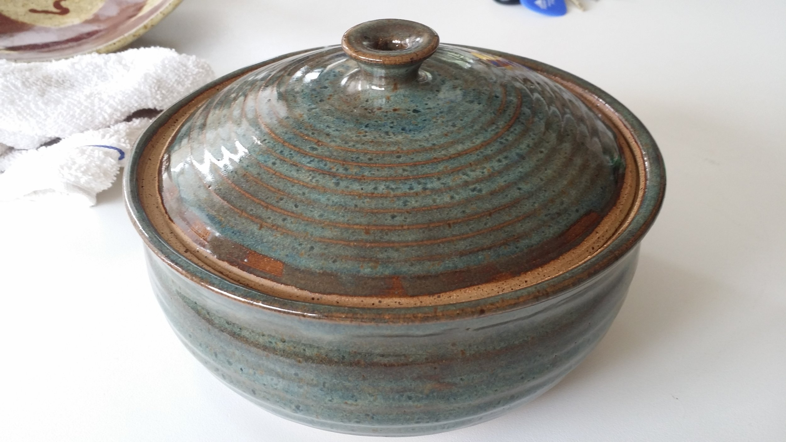 This is another multi-process piece. The casserole is thrown on the pottery wheel and the top is thrown on the wheel with a plaster bowl shape mold using calipers to ensure its the right size to fit the casserole base. You form a handle while making the top piece.