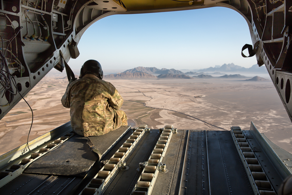 A US Army Soldier and aircrewman sits on the ramp of a chinook helicopter whileflying at 1,500 feet (Lash-e Juwayn, Afghanistan).