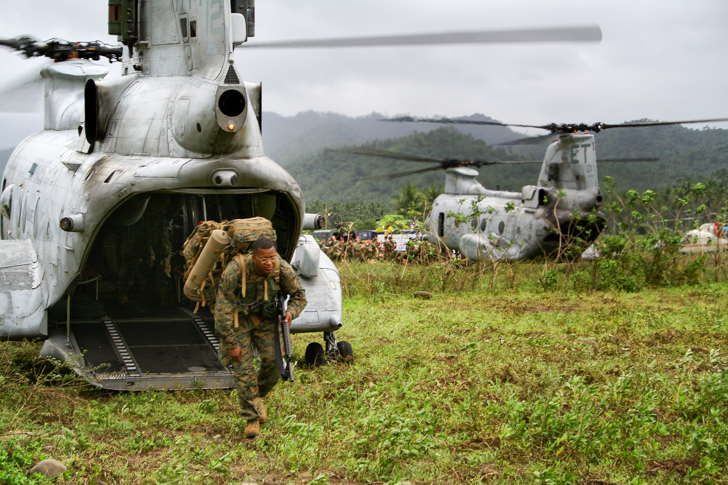 U.S. Navy Hospital Corpsman (medic) exits a helicopter at the site of a landslide on the island of Leyte, Philippines.