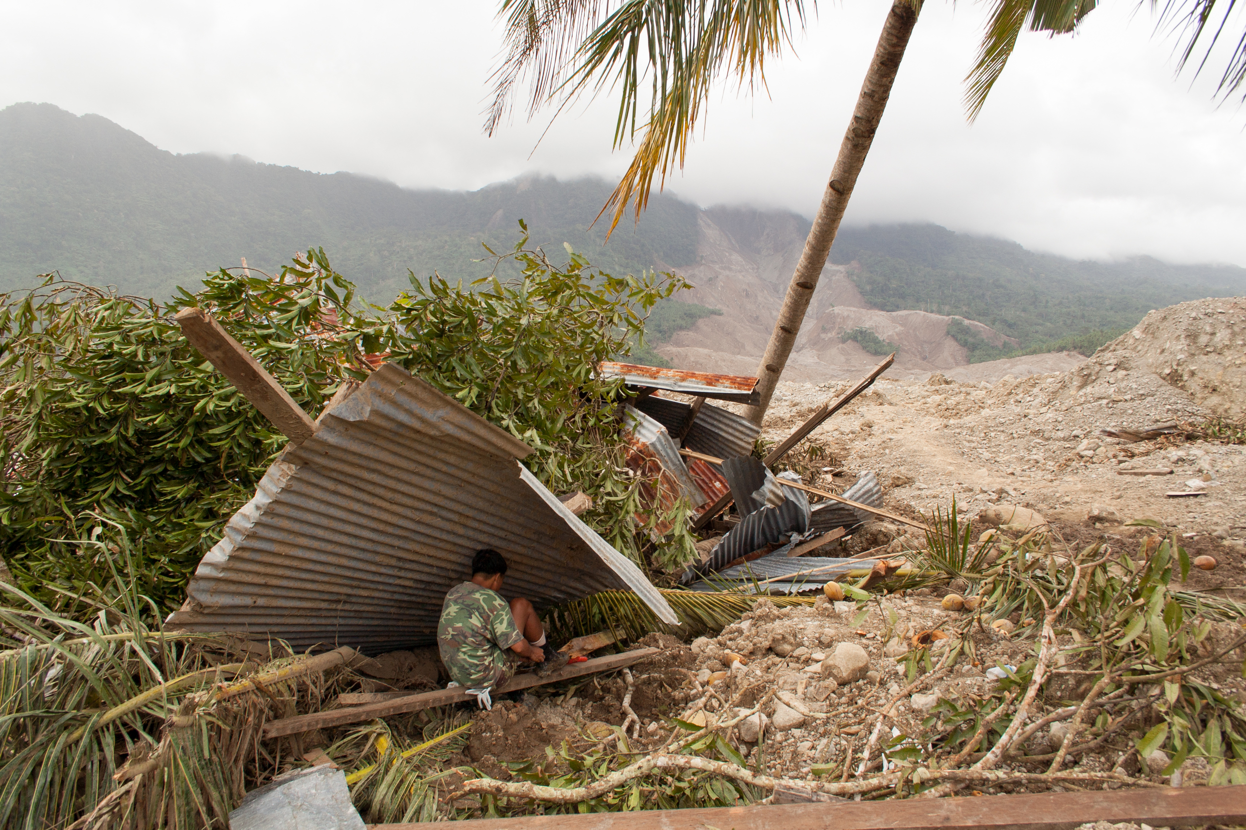 A Filipino Marine takes a break from search operations under what used to be the roof of a building (Guisaugon, Leyte, Philipinnes).
