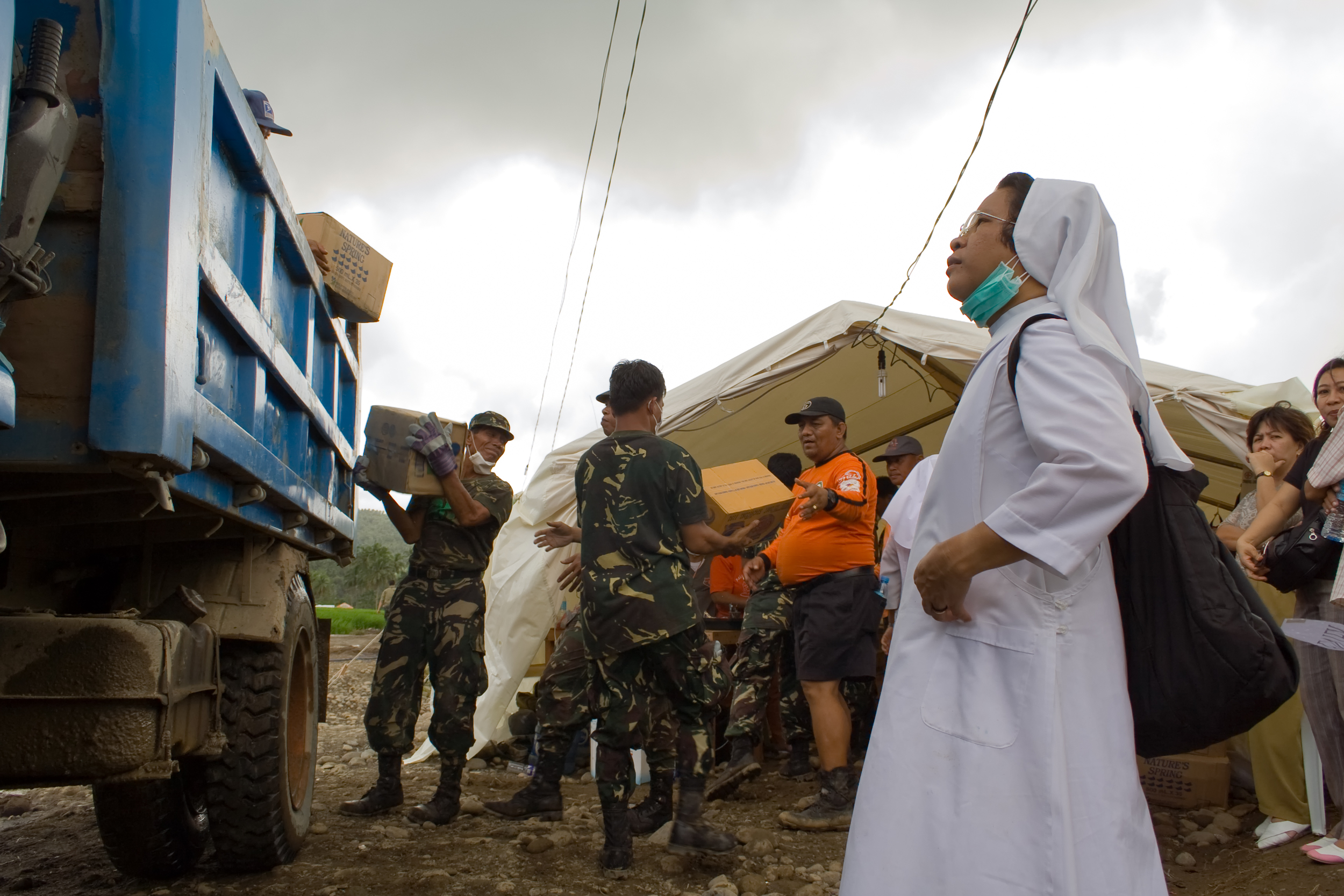 A nun watches as supplies are unloaded at the search operations area in Guinsaugon, Leyte, Philippines.