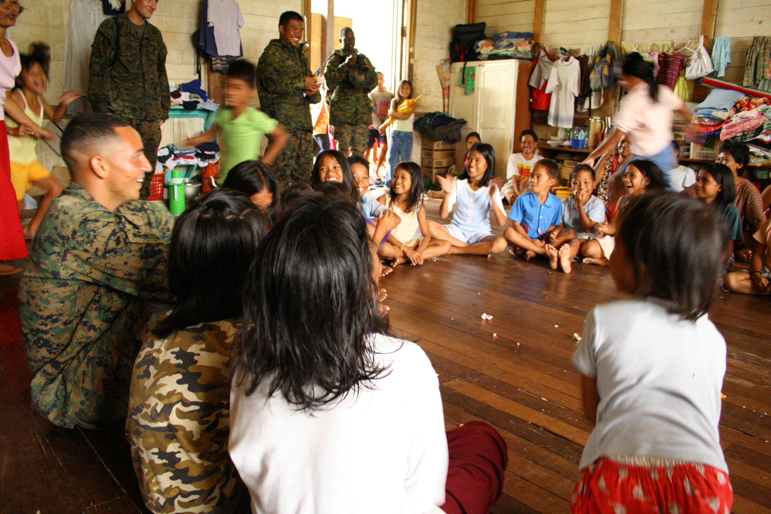 U.S. military personnel play duck-duck-goose with children at the orphanage in Saint Bernard, Leyte, Philippines.