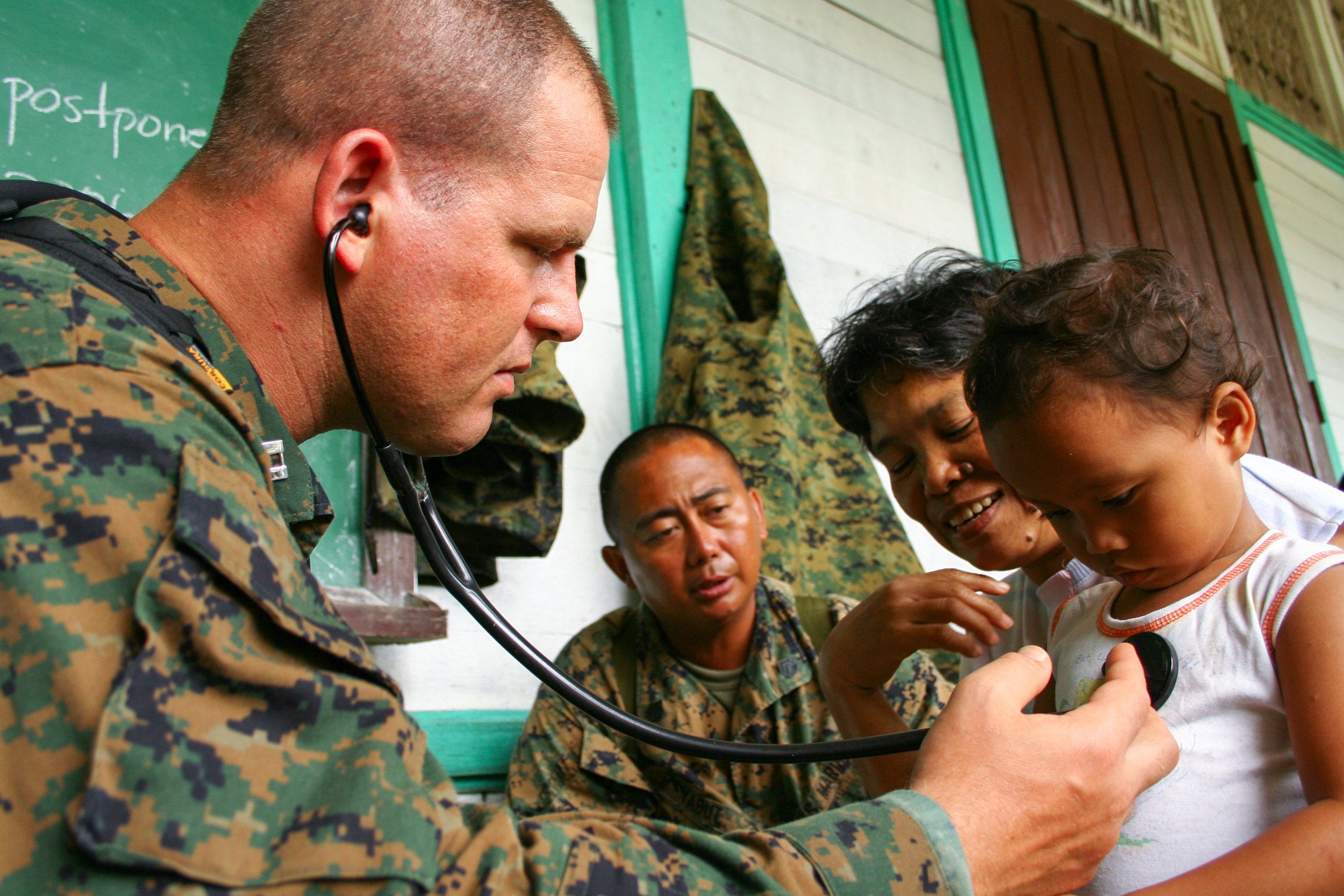 A U.S. Navy doctor performs a check-up on a young Filipino girl at the orphanage in Saint Bernard, Leyte, Philippines.