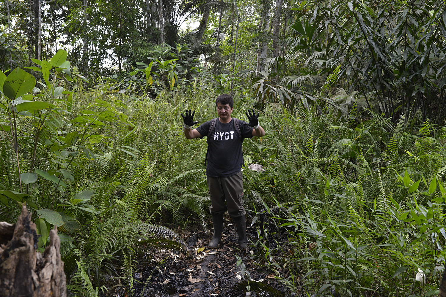 ECUADOR, Lago Agrio. December 2015.  Donald Moncayo, activist and ally of Amazon Watch, stand on an oil 'pool' left by Texaco in 1992 (now Chevron). Donald, a member of the affected communities, dedicated his life to showing the world the environmental disaster left by Texaco.