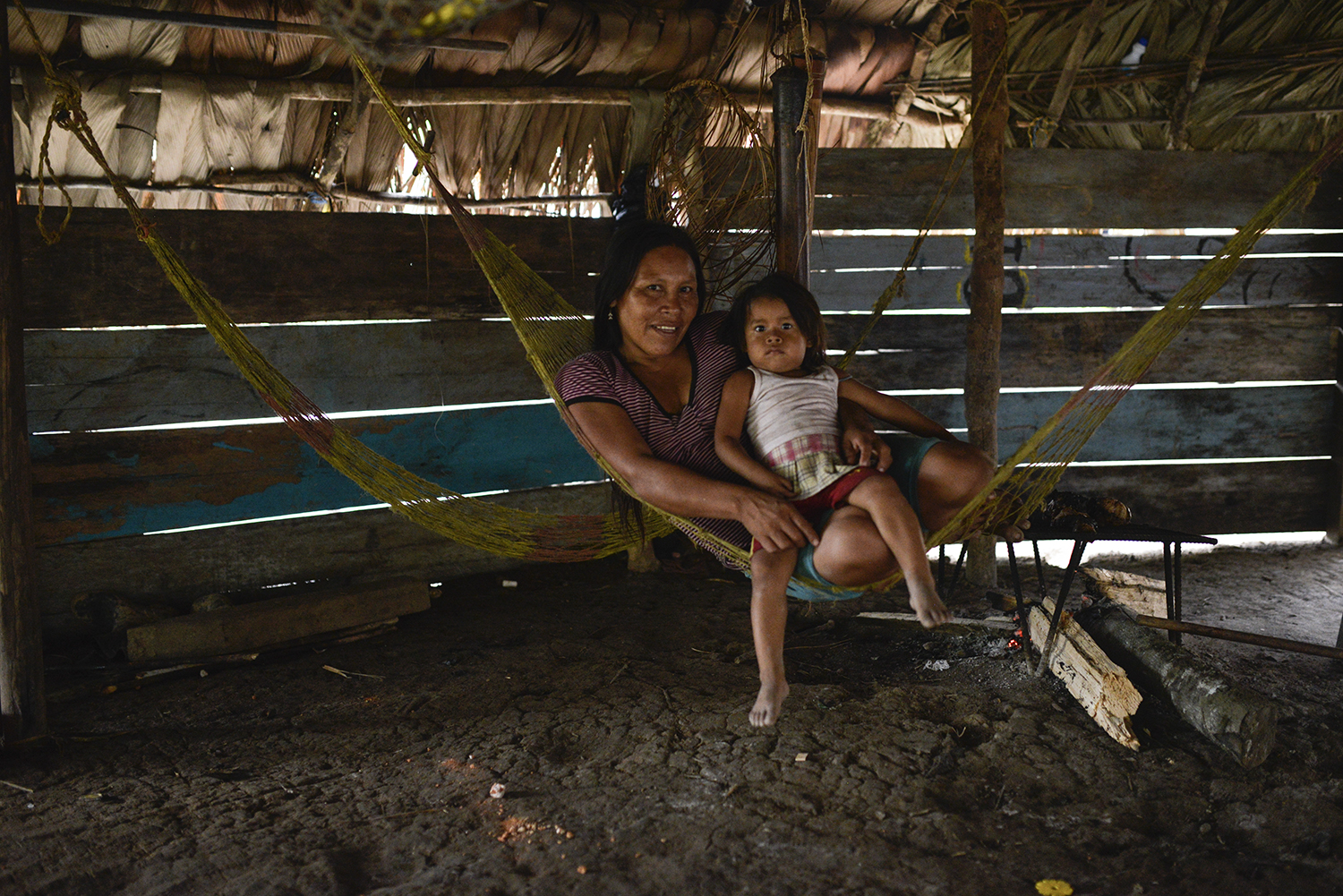 ECUADOR, Yasuni National Park. November 2015.  Numpo and her daughter Jemenca sit on a hammock inside a hut along the river Shiripuno in the Huaorani Reserve of the Yasuni Nation Park. With the construction of the El Auca road, an oil exploration road built in the 1980s during the oil boom of the region, the Huaorani tribe was pushed out and forced to move deeper in the rainforest.