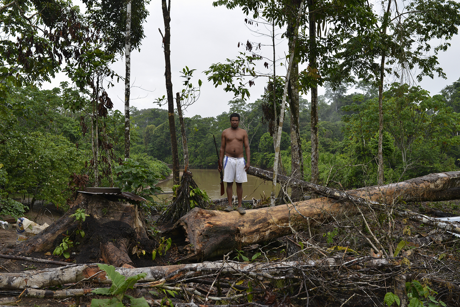 ECUADOR, Yasuni National Park. November 2015.  Juan Carlos Arvalado, a woodcutter and hunter, holds a rifle along the banks of the river Shiripuno. Texaco dumped 18 million of gallons of toxic waste directly into the rivers and soil of the Ecuadorian rainforest affecting hunting, fishing and consequently the lives of residents themselves.