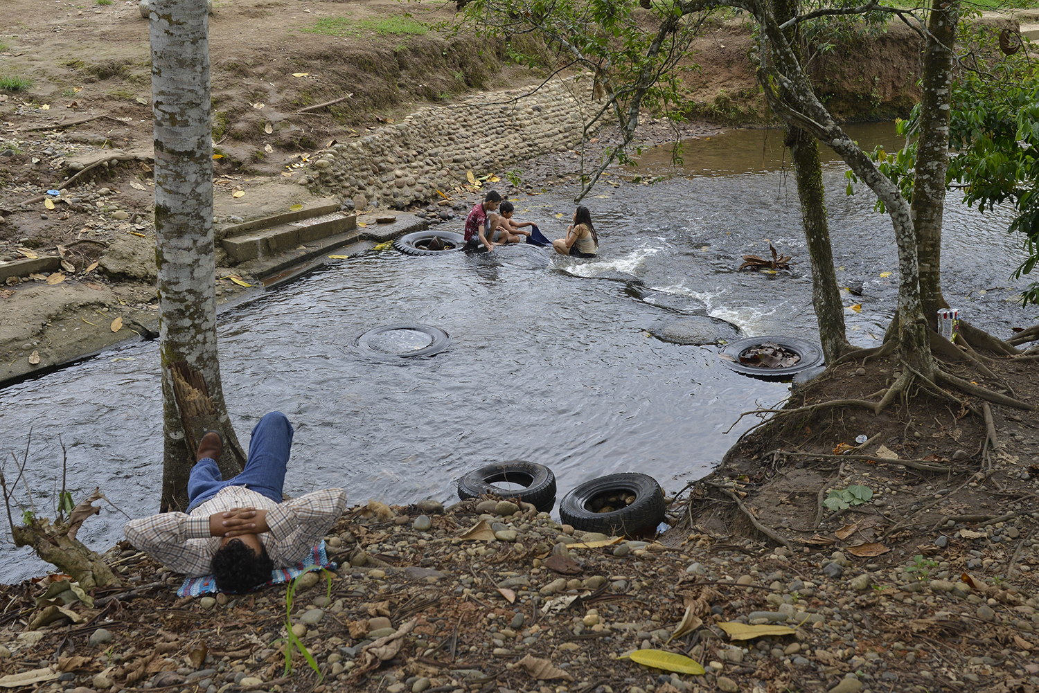 ECUADOR, Sucumbios Province. December 2015.  Children wash clothes in a river in the Lago Agrio Canton. Drinking, bathing and fishing in contaminated rivers has led to stomach and skin cancers, abortions, infections and headaches.