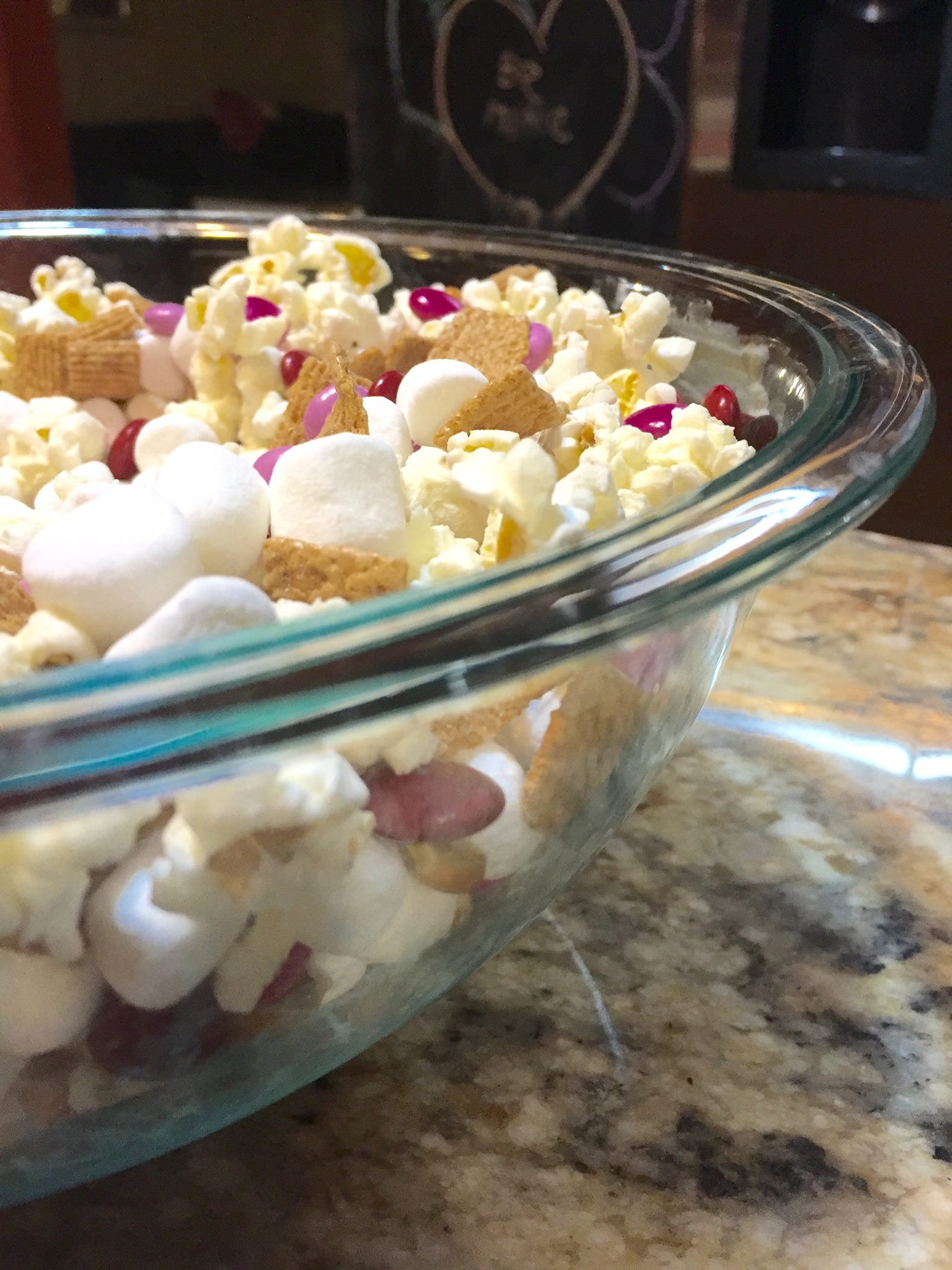 Valentines Day popcorn for our special movie night. Ingredients include golden grahams, mini marshmallows, and valentine m&ms.