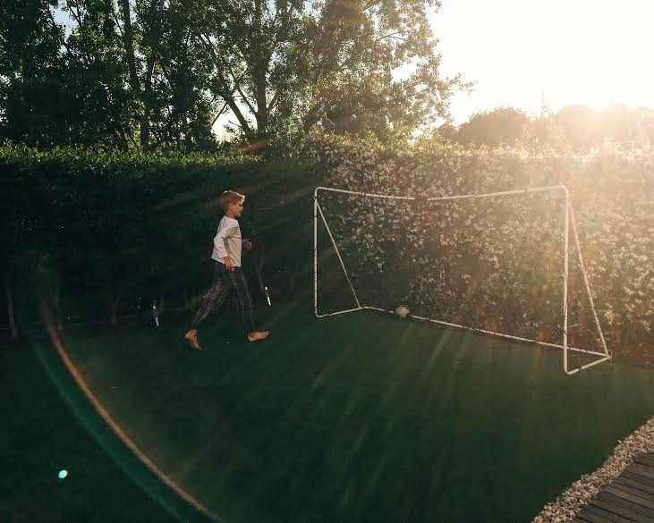6.28 / 8:54 post meridiem // We had just finished dinner and Alvaro ran outside to play. I love this photo because you see the sunset and the beautiful honeysuckles behind the goal.