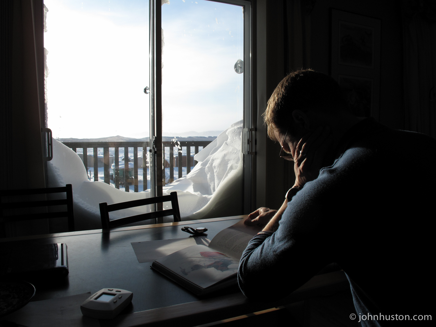 Tyler reads a book in Norwegian about a 2006 unsupported North Pole ski expedition. Frobisher bay is out the window.