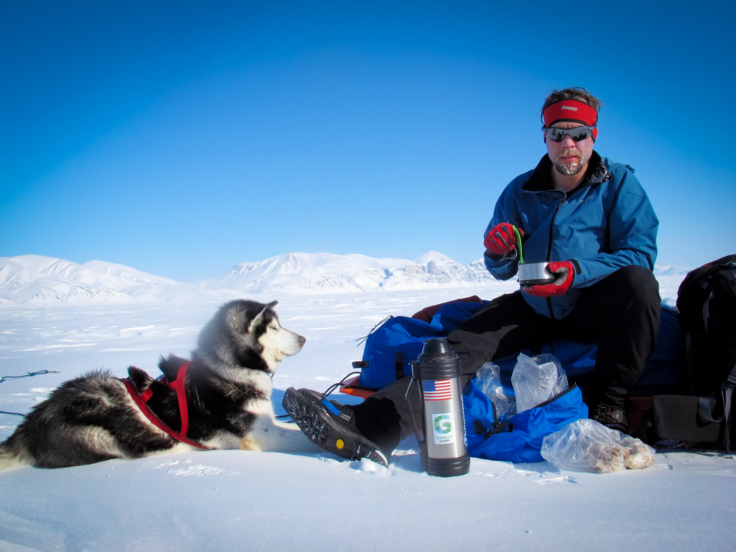 John Huston taking a sustenance break on Canada's Ellesmere Island with his skijor companion Elle. © Tobias Thorleifsson